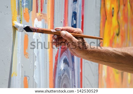 Professional painter at work, painting a street wall - stock photo