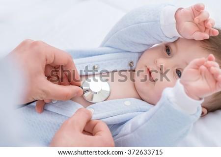 Professional pediatrician examining infant  - stock photo