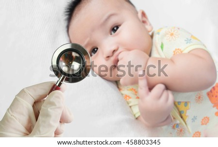 Professional pediatrician examining infant in the hospital. Stethoscope in doctor's hand and Blurred background of cute asian baby on the towel. - stock photo