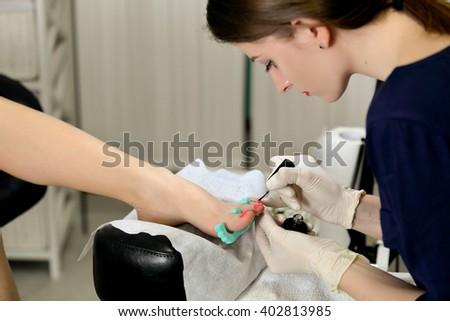 Professional pedicure master making pedicure in salon - stock photo