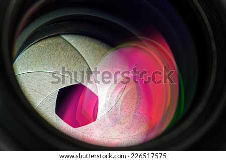 Professional photo lens closeup with colorful reflections. - stock photo