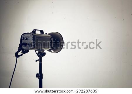 Professional photo studio strobe with reflector on tripod. - stock photo