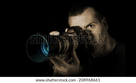 Professional photographer eye in action on a black background.  - stock photo