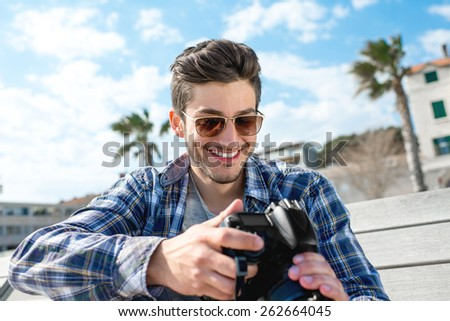 Professional photographer in casual clothes holding camera on the bench in the tropical city