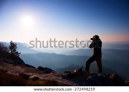 Professional photographer takes photos with mirror camera on peak of rock. Dreamy fogy landscape, spring orange pink misty sunrise in a beautiful valley below - stock photo