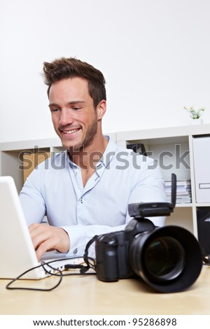 Professional photographer with camera and laptop computer in office - stock photo