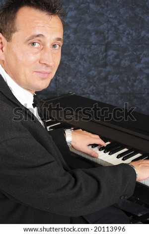 Professional pianist playing the piano during a performance. - stock photo