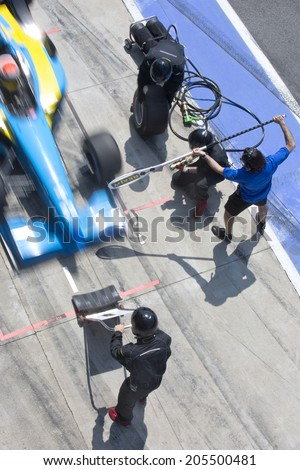 Professional pit crew ready for action as their team's race car arrives in the pit lane during a pitsstop of a car race, concept of ultimate teamwork - stock photo