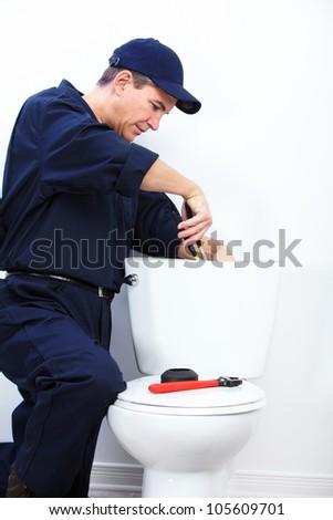 Professional plumber doing toilet reparation. Plumbing repair service. - stock photo