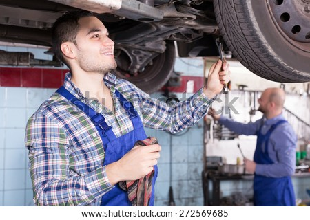 Professional positive serviceman  repairing car of client  - stock photo