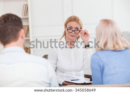 Professional psychologist is giving advice to young married couple. She is sitting and touching her eyeglasses. The woman is looking at the family with joy - stock photo