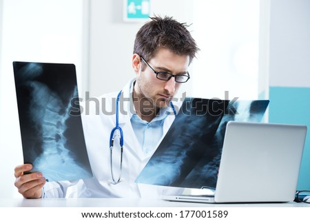 Professional radiologist examining an X-ray image of human spine. - stock photo