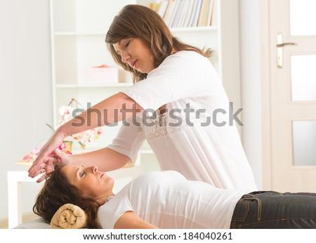 Professional Reiki healer doing reiki treatment to young woman - stock photo