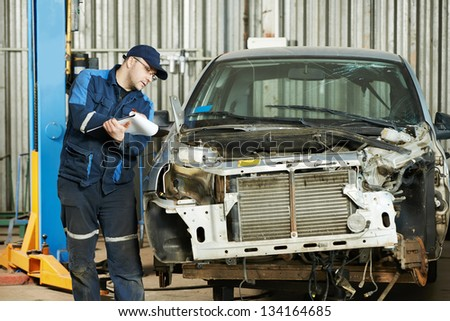 professional repairman worker in automotive industry at repair determination of damaged metal body car - stock photo