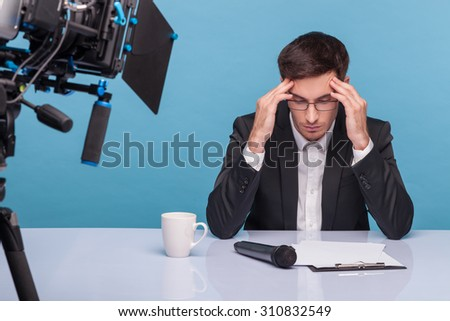 Professional reporter has a terrible headache. He is sitting at the table and touching his temples. The man is looking down at the documents with frustration. Isolated on blue background - stock photo