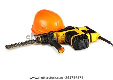 professional rotary hammer drill and a construction helmet on a white background. - stock photo