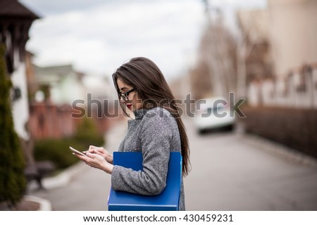 Professional saleswoman, people concept - happy businesswoman with folder and mobile phone over property background