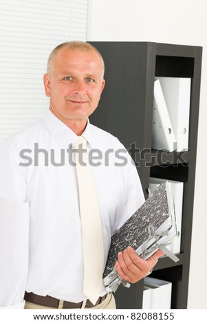Professional senior mature businessman standing in office holding folders