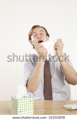 professional sitting at desk sneezing into tissue - stock photo