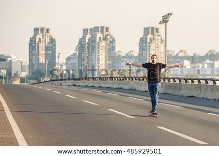 Professional skateboarder riding a skate over a city road bridge, through urban traffic. Free ride skateboards