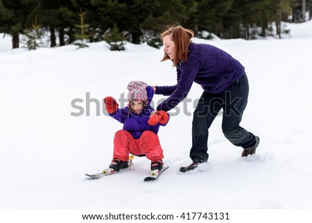 Professional ski instructor is teaching a child to ski on a sunny day on  a mountain slope resort with sun and snow. Family and children active vacation. - stock photo