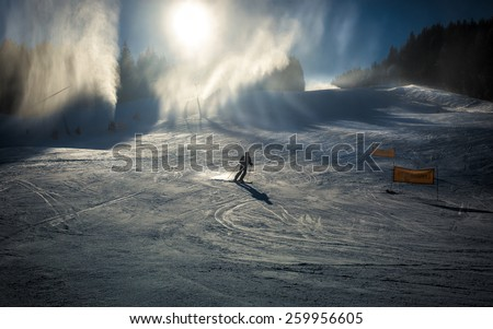 Professional skier going down the slope under working snow cannons - stock photo