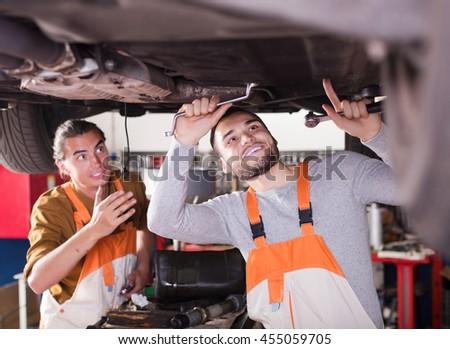 Professional smiling mechanics repairing car of client - stock photo