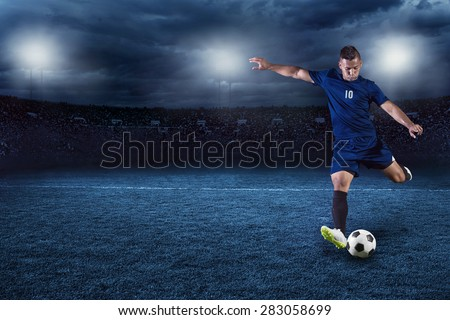 Professional soccer or football player during game in full floodlit stadium at night - stock photo