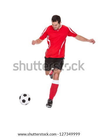 Professional soccer player kicking ball. Isolated on white - stock photo