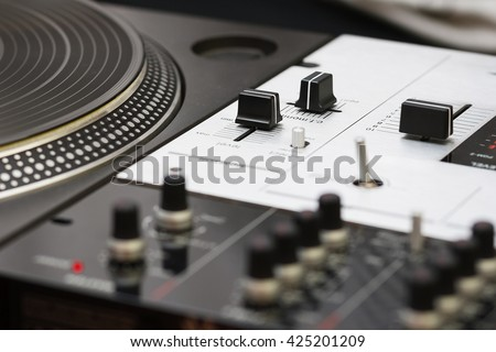 Professional sound mixing controller and turntable vinyl record player. Good for DJ playing music on concert, event and scratching. Macro focus on knobs,regulators - stock photo