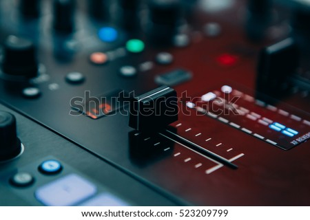 Professional sound mixing controller for hip hop dj specialized on scratch records,mix live music at party.Audio mixer knobs and faders in focus.Disc jockey mixer with volume regulator knob fader