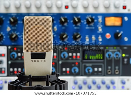 Professional studio microphone and a rack of audio devices, with shallow focus - stock photo