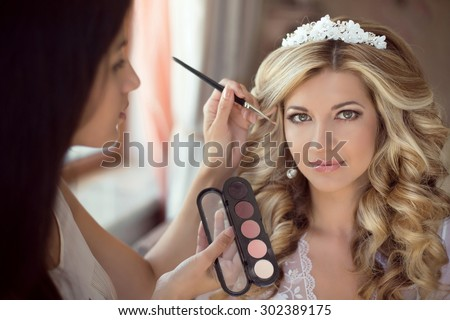 Professional Stylist makes makeup bride on the wedding day. Beautiful smiling blond woman with long curly hair style. - stock photo