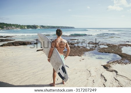 professional surfer holding a surf board man - stock photo