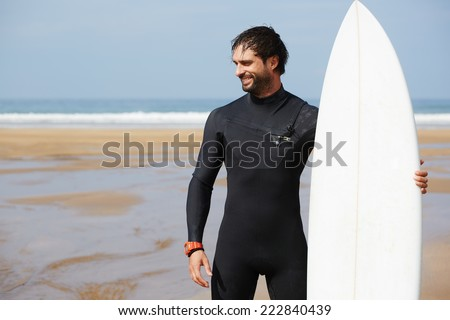 Professional surfer man dressed in wetsuit ready to surfing on big waves, as sunny summer day attractive brunette surfer smiling standing on the sand, young surf man waiting for the waves to surfing - stock photo