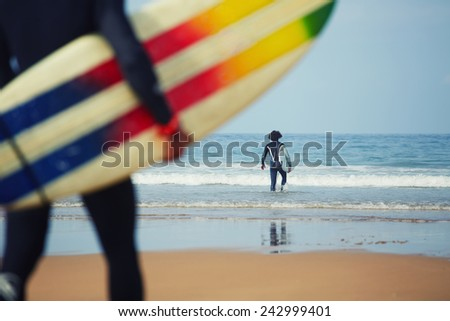 Professional surfers carrying their surfboards while going to the sea, professional surfers in black diving suits ready to surf walk to the ocean, close up of surfboard with surfer on background - stock photo