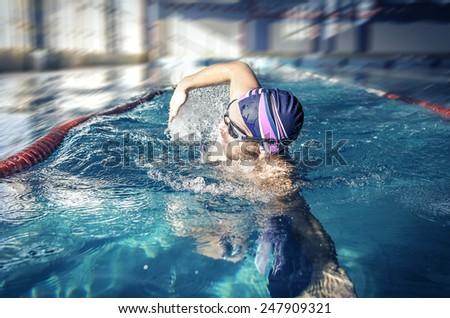 Professional swimmer crawl freestyle in a swimming pool - stock photo