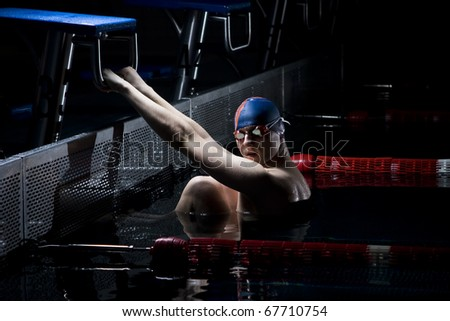 Professional swimmer holding start bar - stock photo