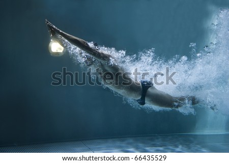 professional swimmer underwater after the jump - stock photo