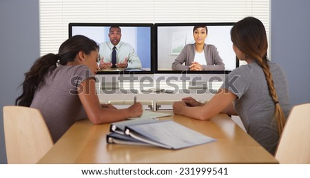 Professional team of multi-ethnic business colleagues having a video conference - stock photo