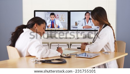Professional team of multi-ethnic medical doctors having a video conference - stock photo