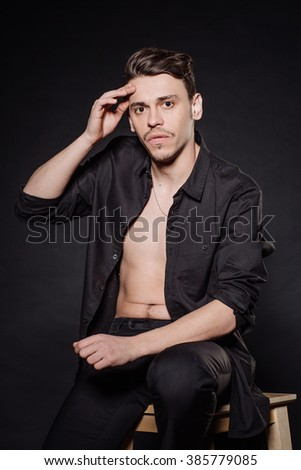 Professional theatre actor in black suit performing on stage. emotions, facial expressions, feelings, body language, signs. image on a black studio background. photo for magazines and websites.