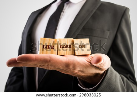 Professional therapist holding three wooden cubes in the palm of his hand reading Life goes on motivating you to make peace with your past and leave it behind in order to fully live the present. - stock photo