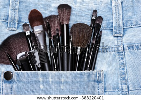 Professional tools of make-up artist in shabby jeans pocket. Sponge tip applicators and various makeup brushes: for applying foundation, powder, blush, eyeshadow, eyebrow brushes and others - stock photo