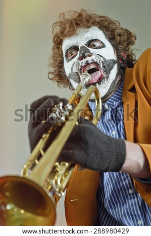 Professional trumpet player with face painted as human skull