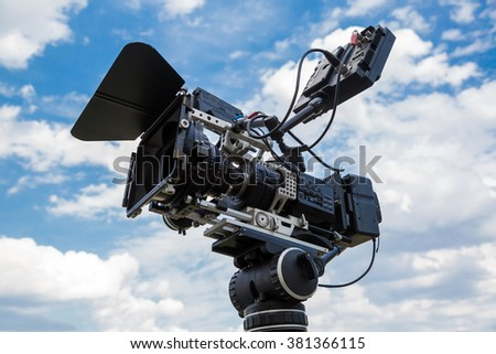 Professional video camera on a tripod against the blue sky - stock photo