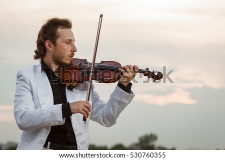 Professional violinist in profile outdoors