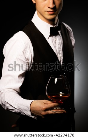 professional waiter in uniform is serving brandy - stock photo