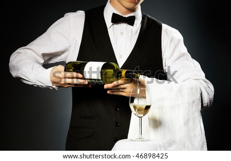 professional waiter in uniform is serving white wine - stock photo