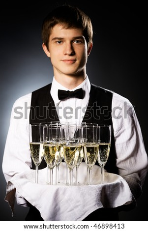 professional waiter in uniform is serving wine (focus on glasses) - stock photo